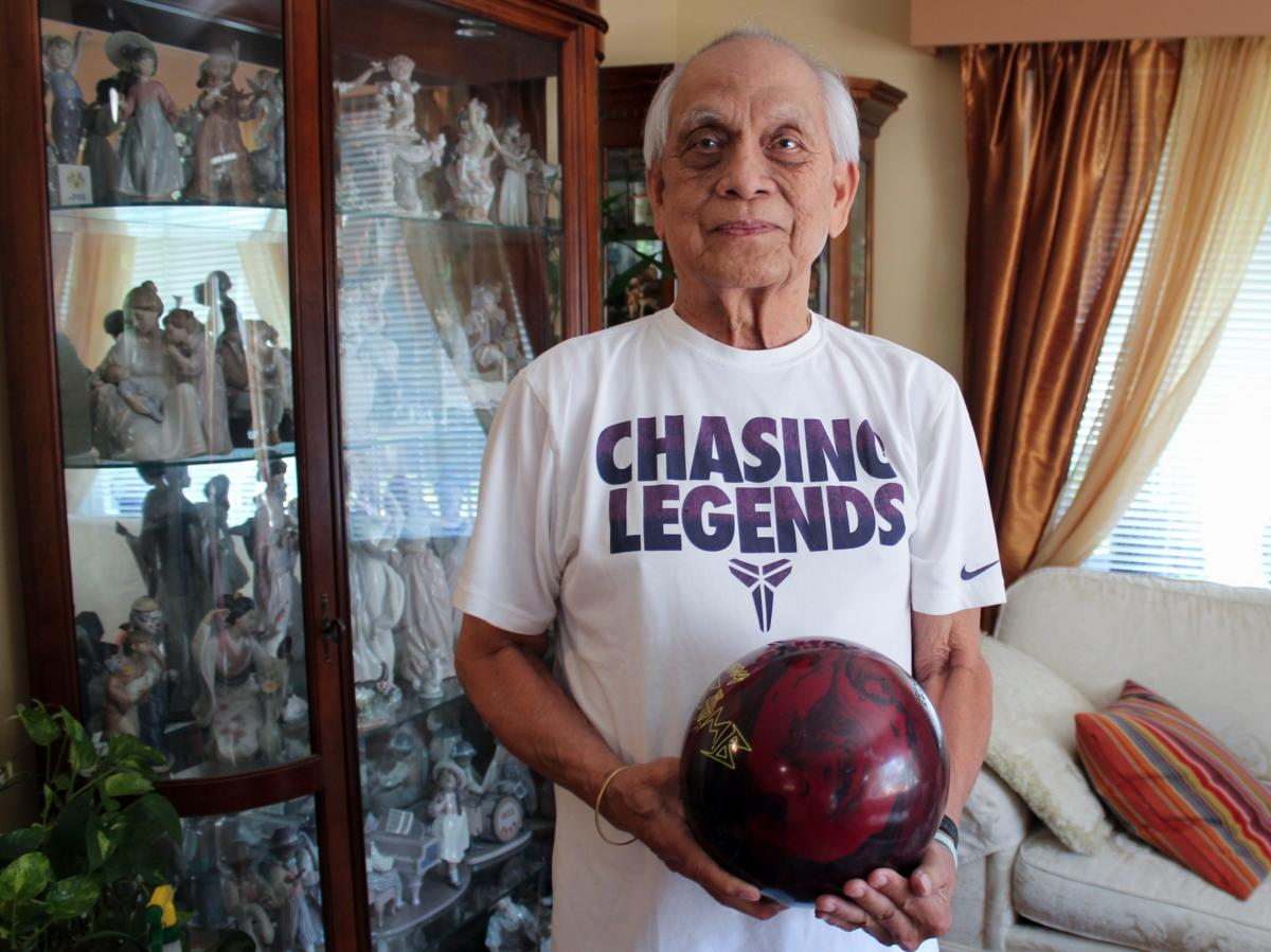 Alex Padua, who was an avid bowler at Naval Support Activity Bethesda, poses with his bowling ball at his home in Wheaton, Md.