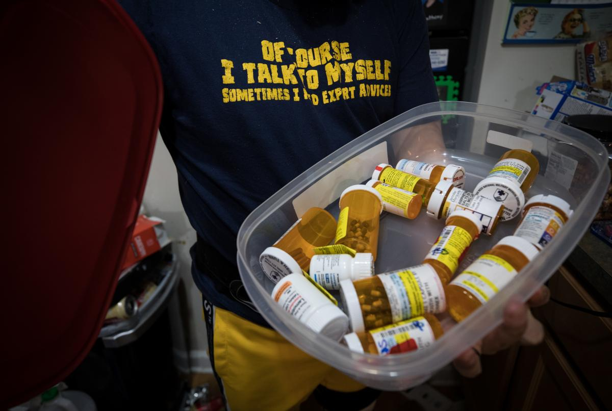 Marquette looks through some of the myriad medications he takes.