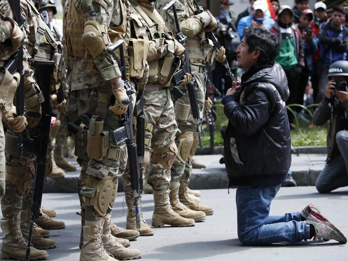 A backer of Bolivia's former President Evo Morales kneels in front of soldiers guarding a street in downtown La Paz, Bolivia, on Nov. 15. A few days earlier, the military advised Morales to resign.
