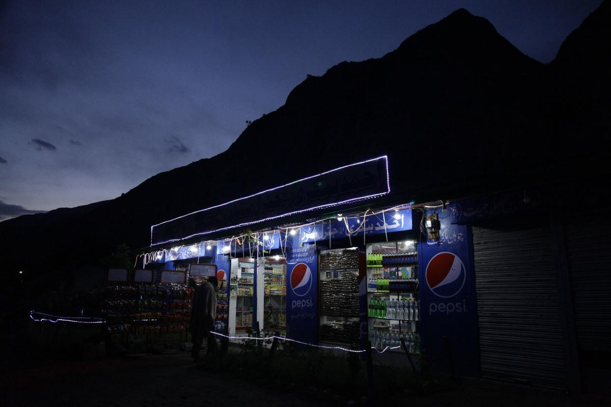The fluorescent lights of a tea shop and grocery store light the Karakoram Highway, which is often flanked by looming mountain ranges.