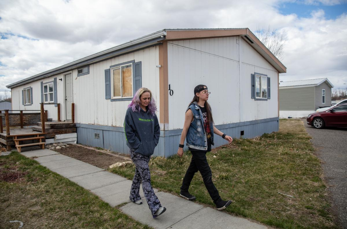 Gaught and her son, Izaah, check on their old home for notices left on the door. Gaught and her family were evicted from the home in a mobile home park in Billings, Mont., owned by Havenpark Communities. The company filed an eviction case against her in N