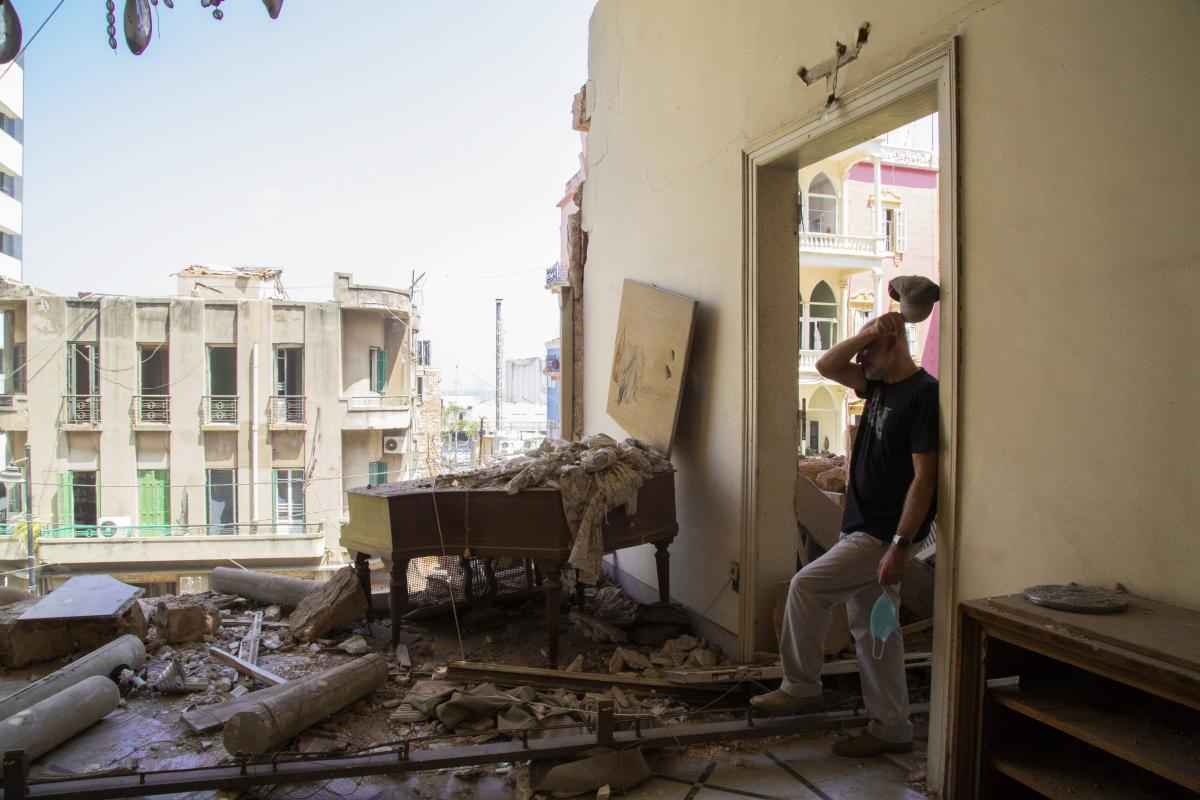 Riad al-Assaad, an engineer, stands in front of the severely damaged residence that belonged to his wife's ancestors, Villa Sehnaoui. He has been working day and night to clean and rebuild it.