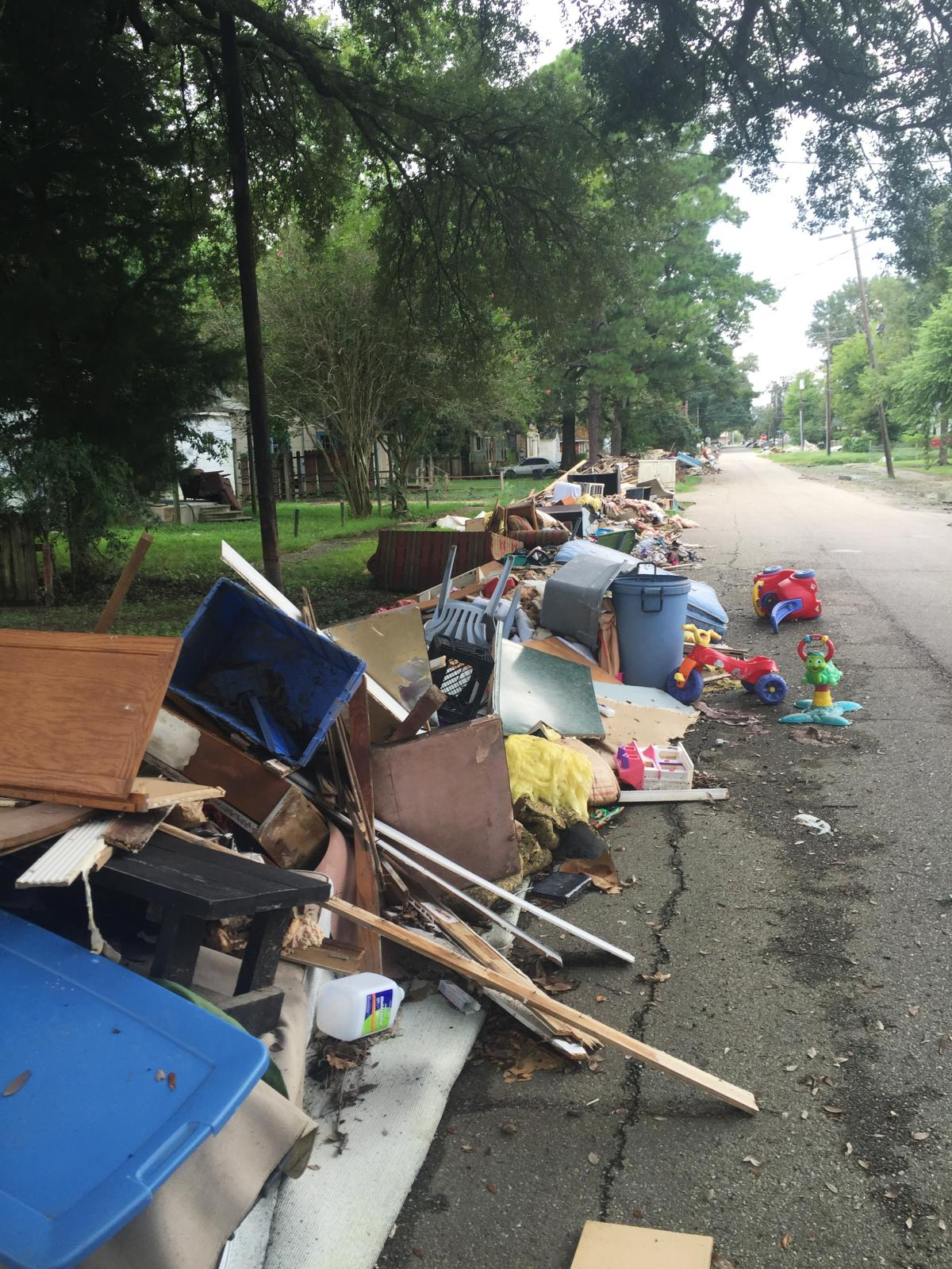 Flood-damaged debris lines a street in Baton Rouge near Claiborne Elementary, which is reopened and hosting students displaced from a nearby school.