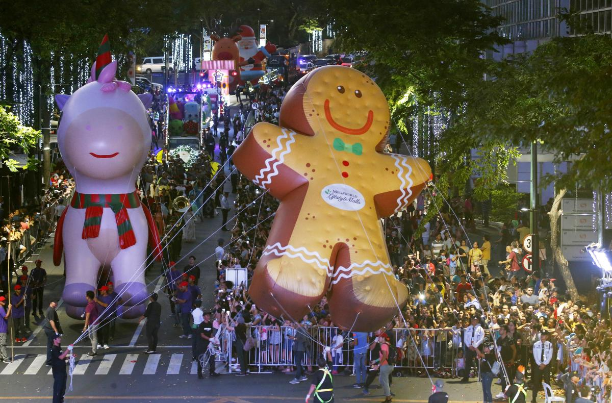 """Hundreds of residents watch as colorful floats and larger-than-life balloons, including the """"Happy Pink Unicorn"""" and the """"Giant Ginger Bread,"""" are paraded ahead of the Christmas celebration at a shopping area in greater Manila, Philippines, on Dec. 8."""