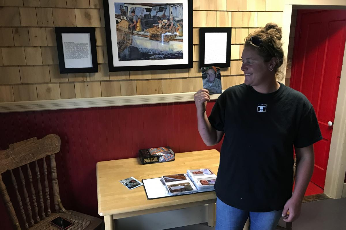 Lobsterman Meredith Oliver with a photo of her grandfather Lee, who taught her to fish and whose lobster boat she inherited at age 15 after his death. Now she's 28 and her plan is to do whatever it takes to keep lobstering.
