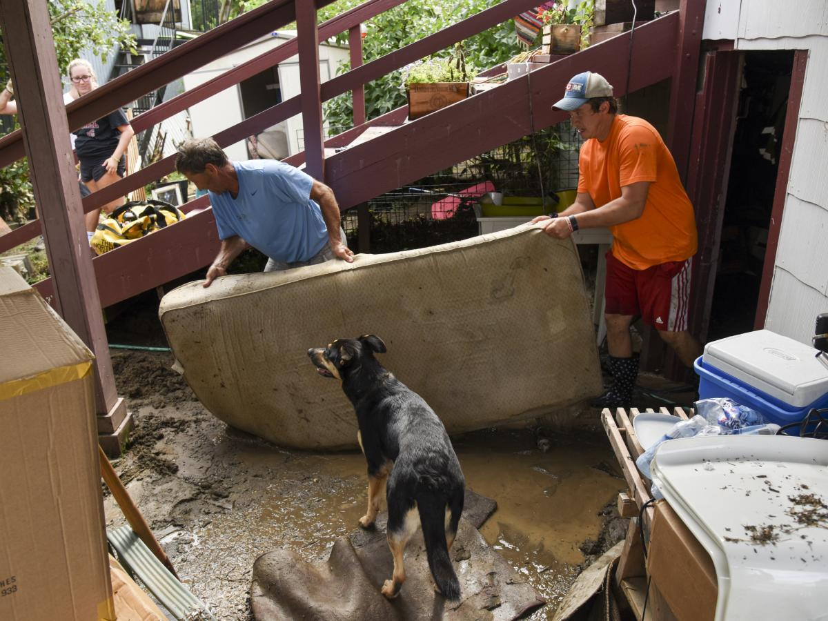 Al Miller (left) helps clear Dan Durantaye's flooded basement after heavy floods devastated the historic district of Ellicott City on Sunday.