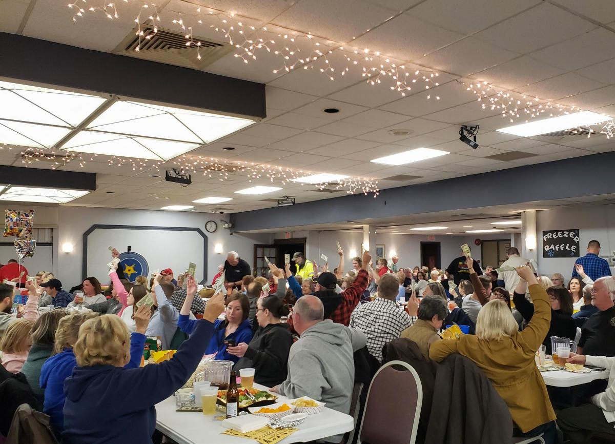 A crowd hoists dollar bills to buy meat raffle tickets at the Polish Falcons Hall in Depew, N.Y.