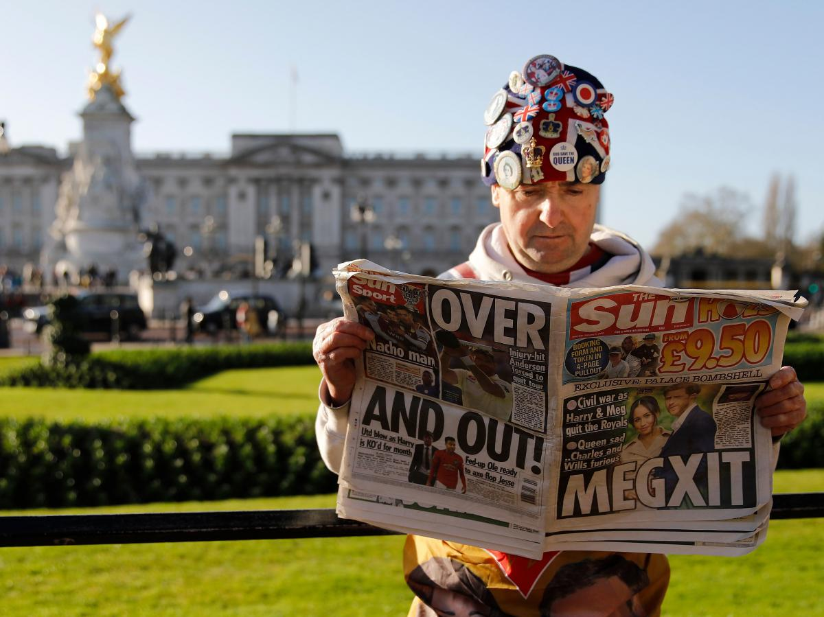 Royal fan John Loughery reads the day's news outside Buckingham Palace in London on Thursday, following the announcement that Prince Harry and Meghan Markle, the Duke and Duchess of Sussex, plan to step down as senior members of the royal family.