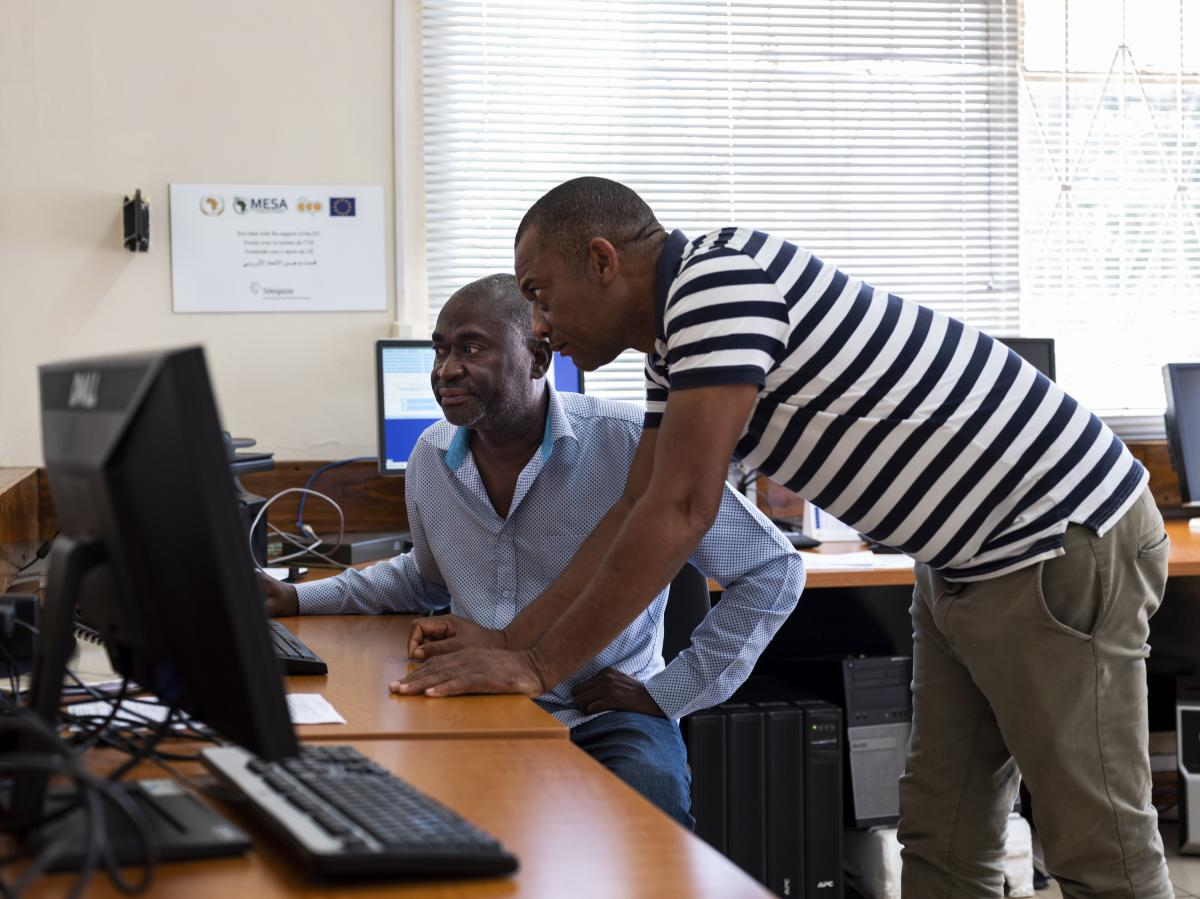Lead forecaster Acacio Tembe (left) discusses issuing a warning about an incoming storm with a colleague at the National Meteorology Institute in Maputo, Mozambique.