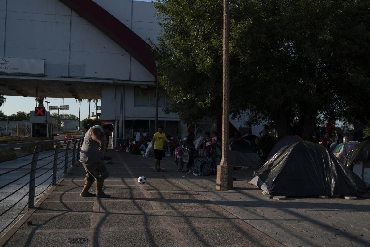 """Asylum-seekers pass their time in an encampment near the Gateway International Bridge in Matamoros, Tamaulipas in September. Most of them have been sent back under the """"Remain in Mexico"""" program."""
