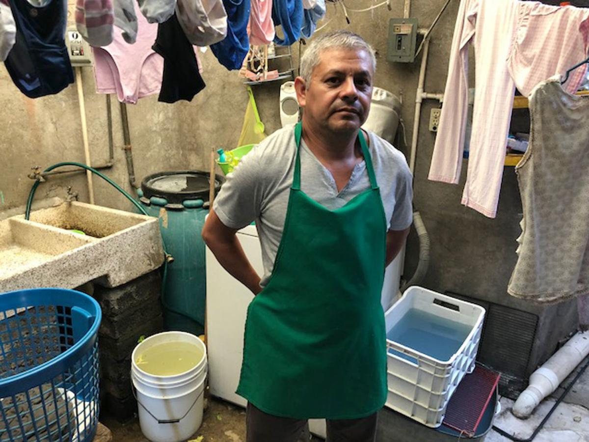 Marco Marquez, 52, keeps storage containers filled with water on his patio. The tap runs dry on a regular basis, but he needs clean water especially for his fruit business.