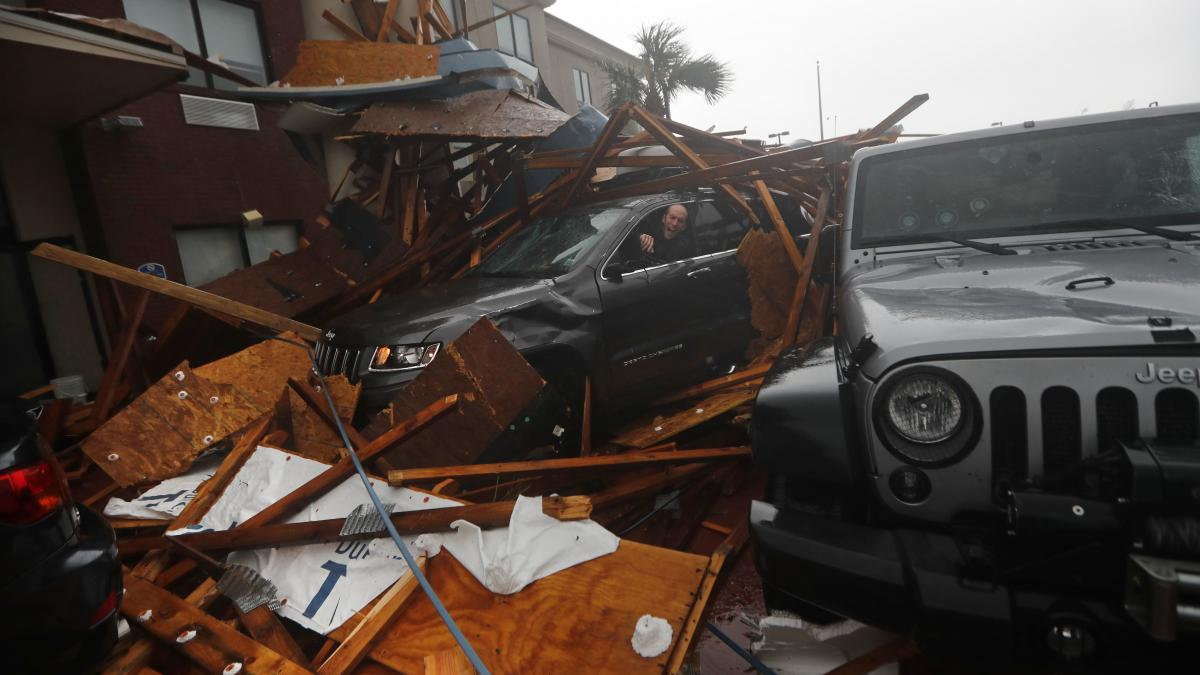 A storm chaser climbs into his vehicle as the eye of Hurricane Michael passes over Panama City Beach, Fla., hoping to retrieve his equipment after a hotel canopy collapsed in the parking area. The storm came ashore as a nearly Category 5 hurricane Wednesd