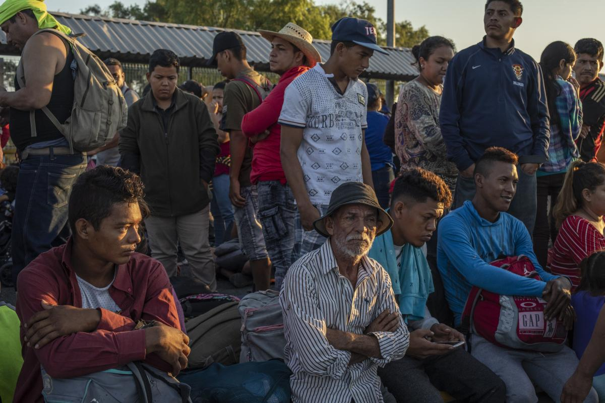 Central American migrants wait to cross into Mexico at Rodolfo Robles International Bridge in Tecun Uman, Guatemala, on Monday.