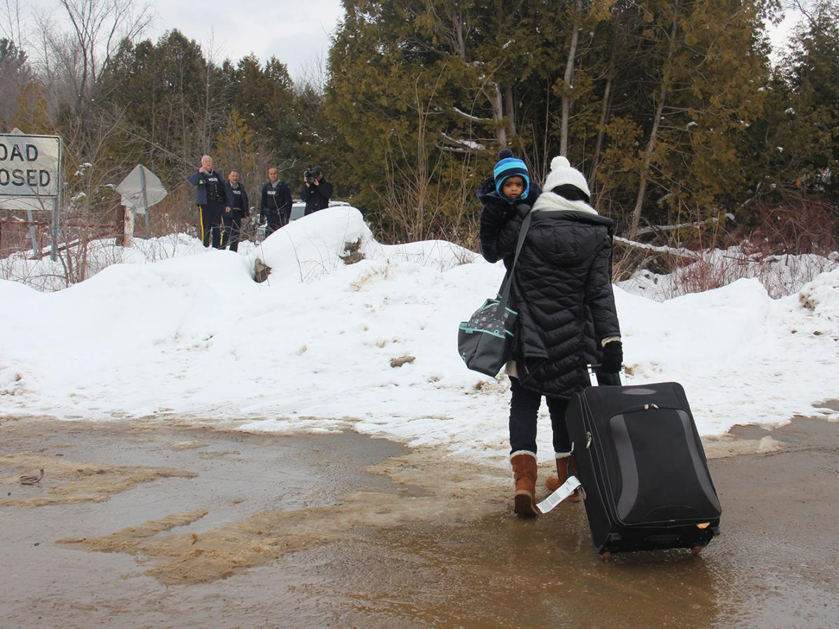 A woman traveling alone with her infant, seeming to understand that she will be arrested, walks toward Canadian police on the far side of the border.