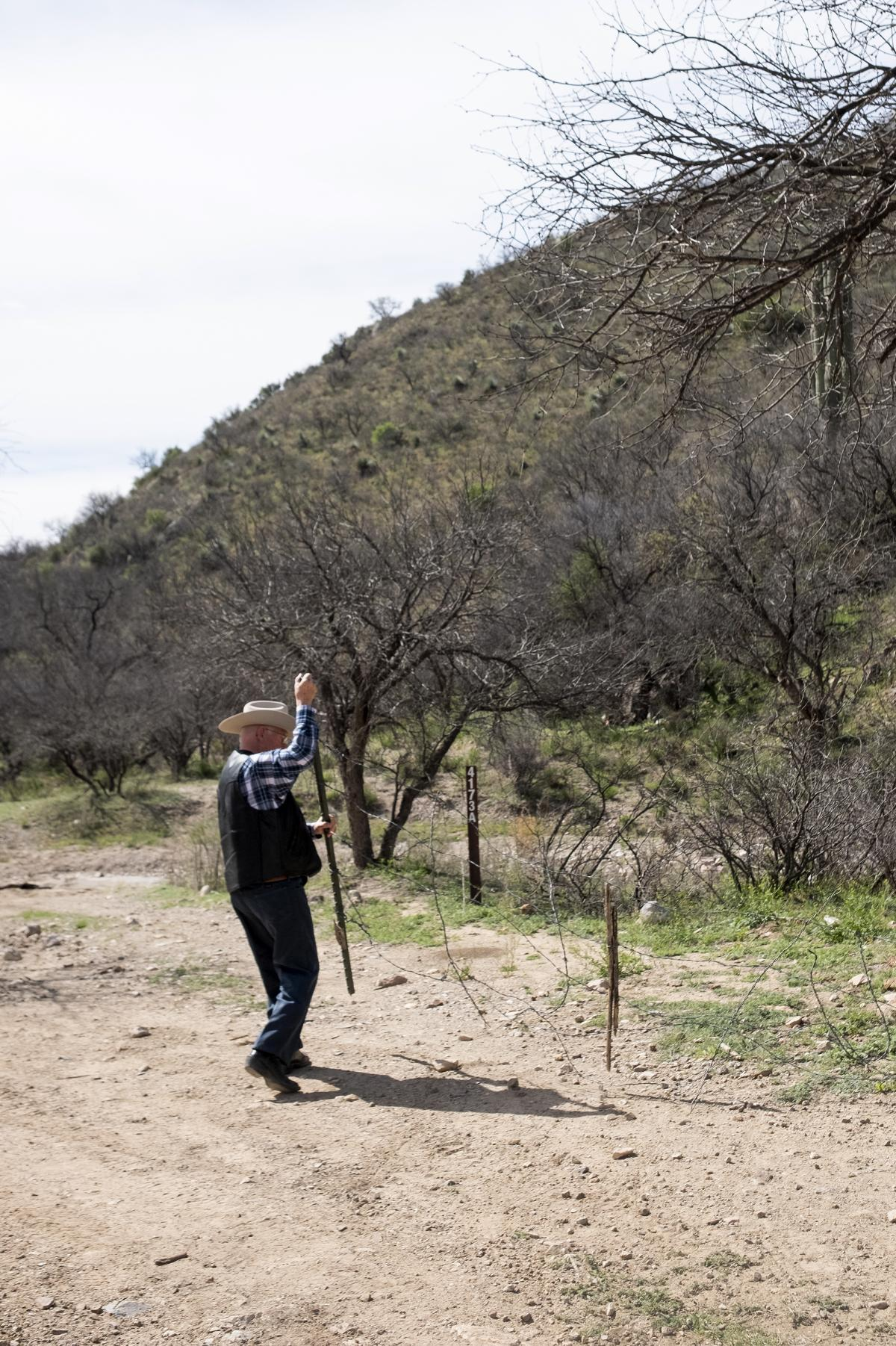 Rancher Jim Chilton opens a gate near the U.S.-Mexico border outside Arivaca. His ranchland  extends five miles along the border, which is marked by a waist-high fence of four strands of barbed wire.