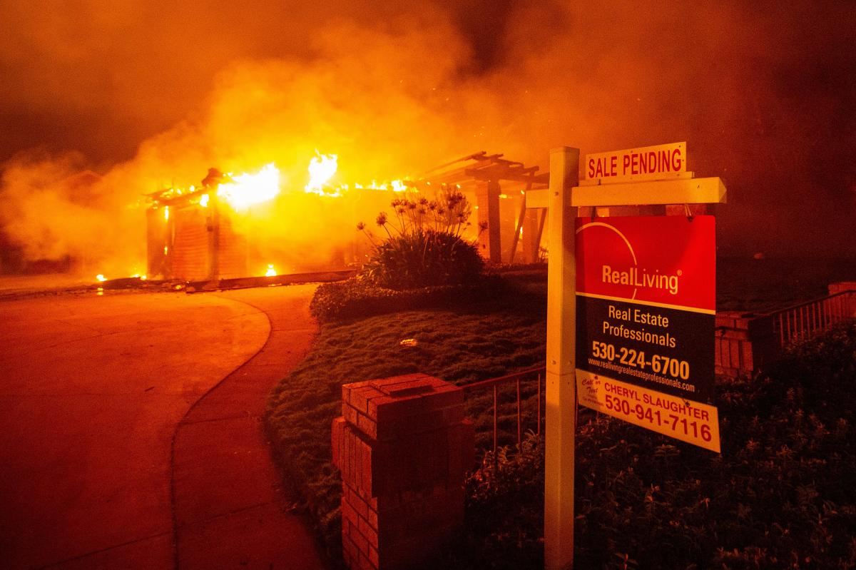 A real estate sign is seen in front of a burning home during the Carr Fire in Redding, Calif., in 2018. More than 1,600 buildings reportedly were destroyed.