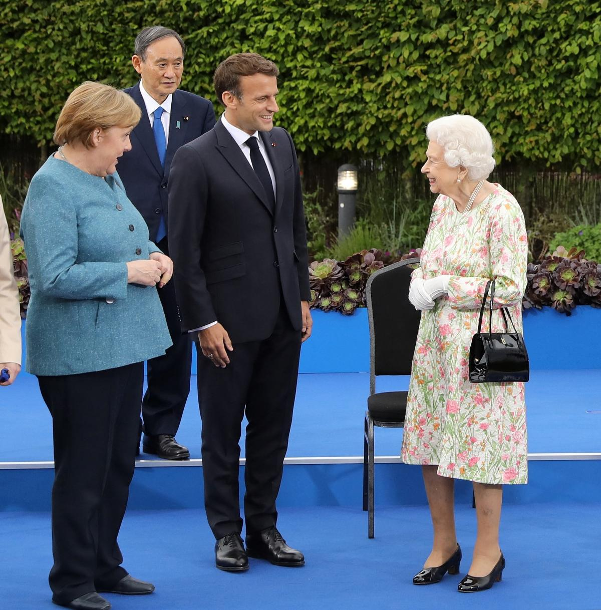 """Queen Elizabeth II with Germany's Angela Merkel, Japan's Yoshihide Suga and France's Emmanuel Macron at a reception Friday. The British monarch joined the G-7 leaders for dinner. """"Are you supposed to be looking as if you're enjoying this?"""" she asked as th"""