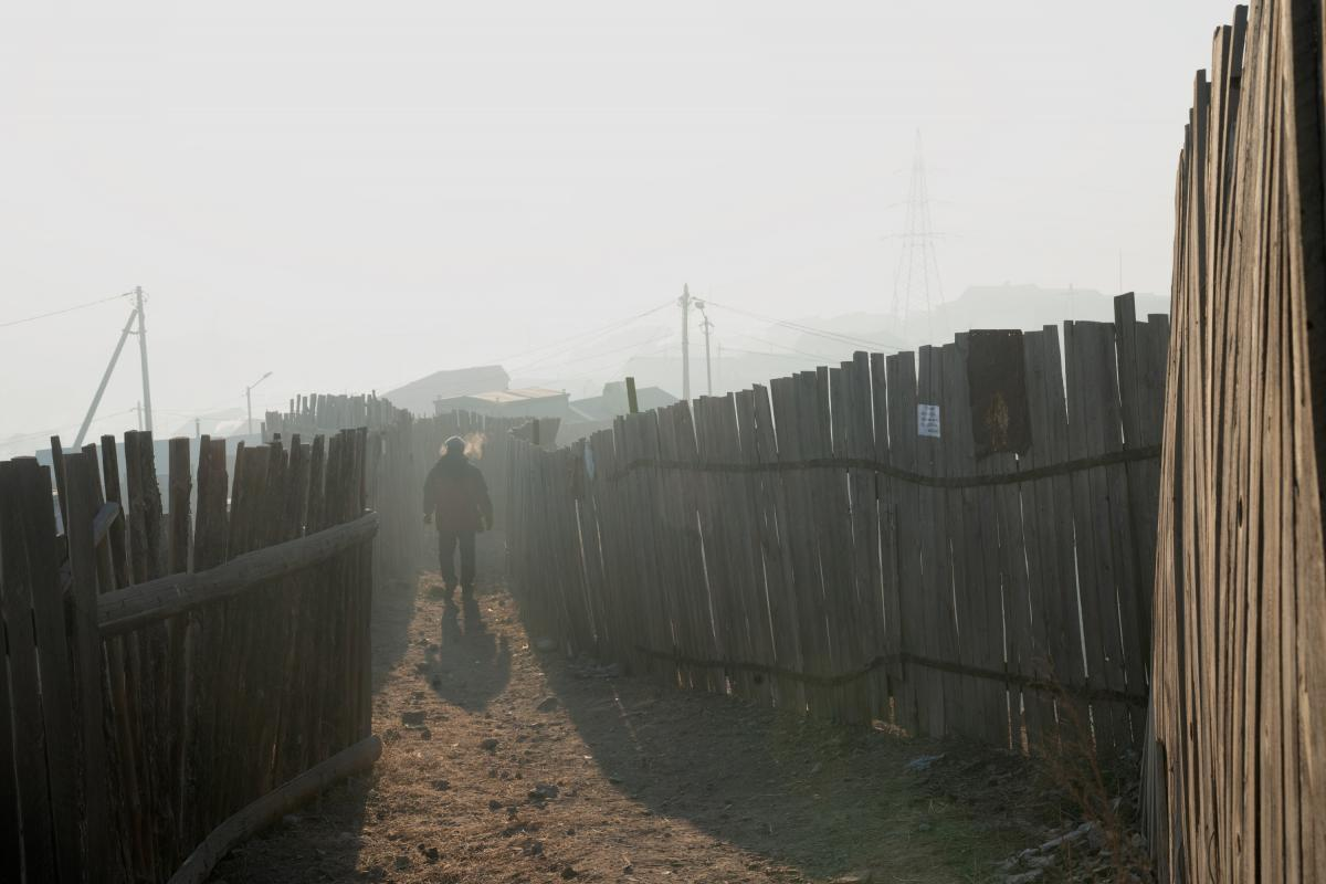 The ger district is unplanned, lacking basic infrastructure. One-third of households live below the poverty line. The sign affixed to the fence says the family is willing to purchase a low-emission stove.
