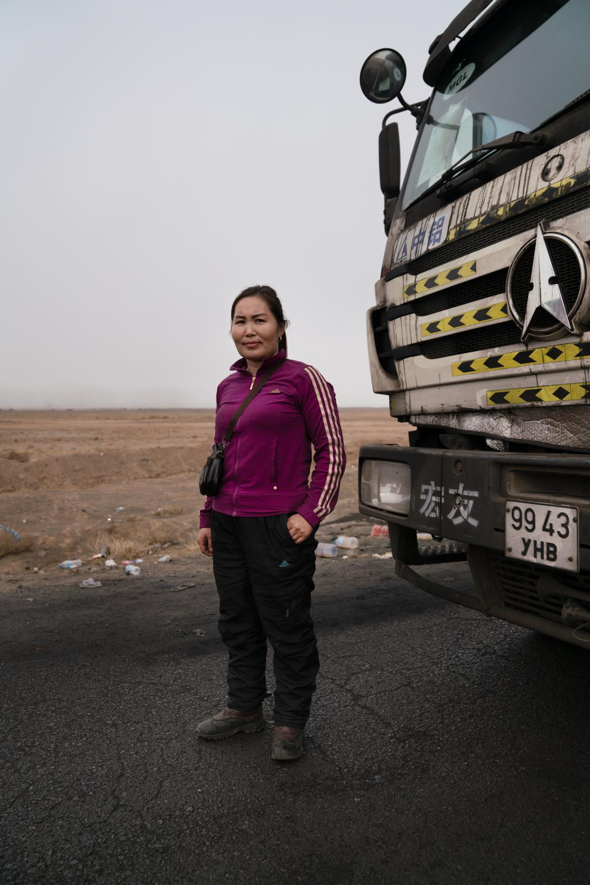 Gulnara Dariiga, 38, stands in front of her truck, a North Benz assigned to her by her Chinese employer. She performs a tea ritual in the morning, praying drivers stay safe on the road.