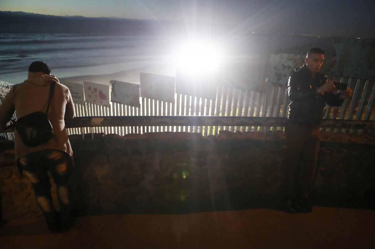 People gather on the Mexican side of the U.S.-Mexico border barrier in Tijuana at the Pacific Ocean Thursday.