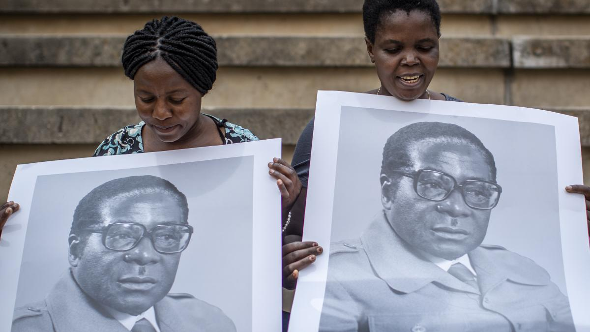 Women in the stands at the National Sports Stadium hold posters of former president Robert Mugabe.