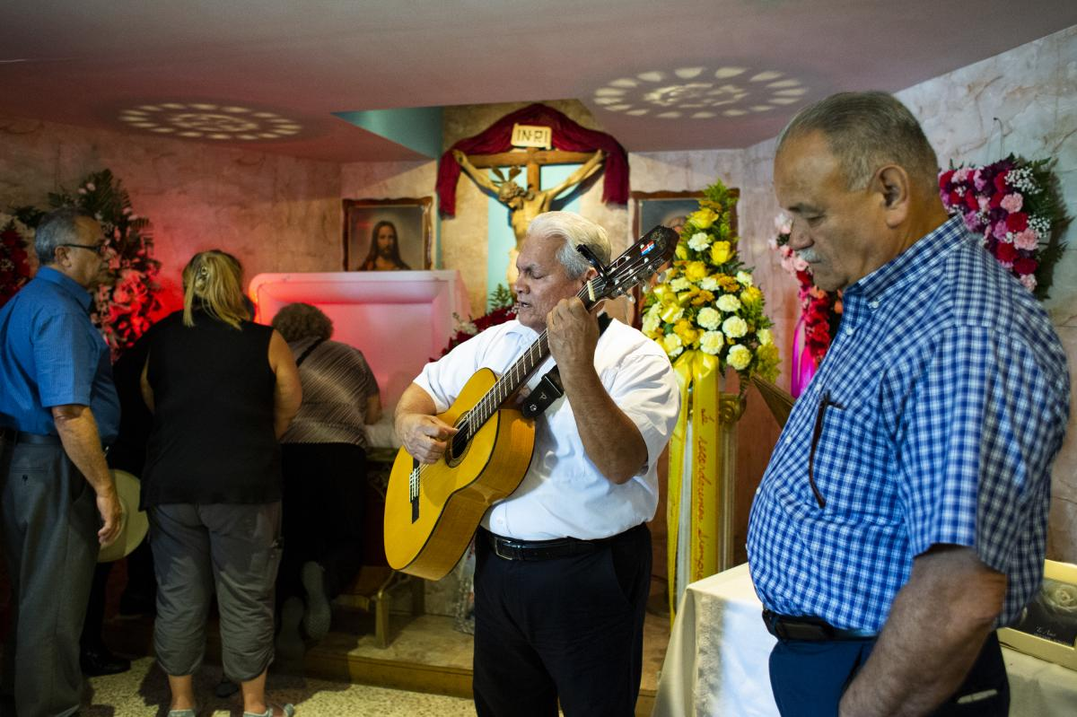 Gary Nuñez (center) sings as family and friends pay their respects at Irizarry's wake.