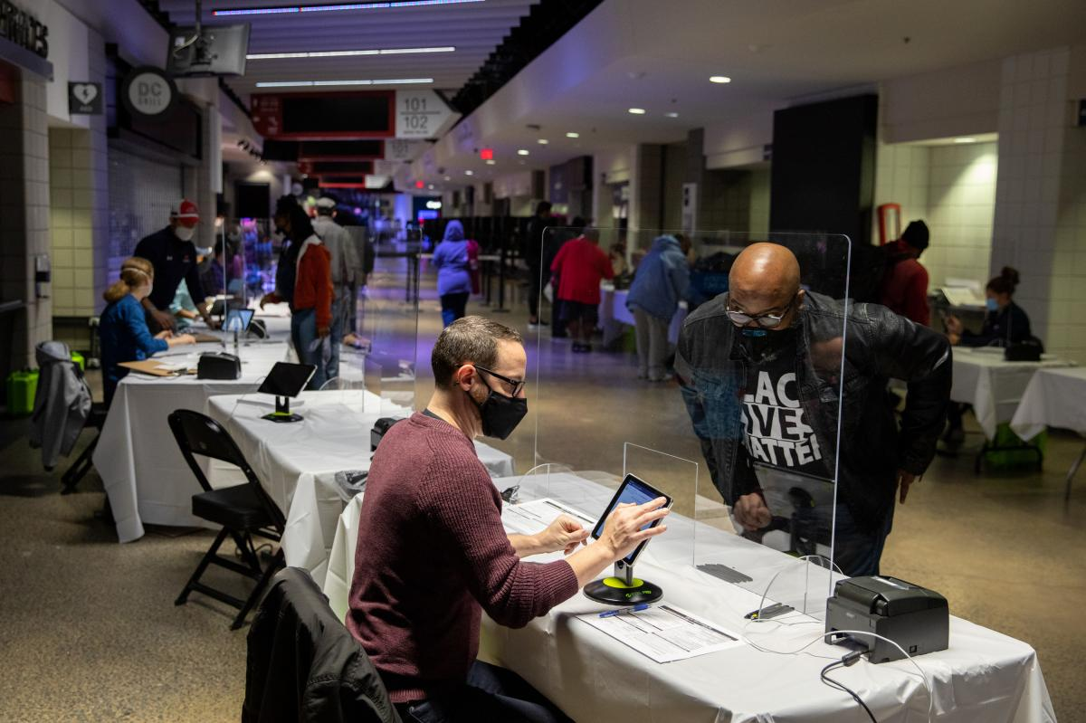 Brian Diem (left) checks in a voter on the first day of early voting at Capital One Arena in Washington, D.C., on Tuesday.