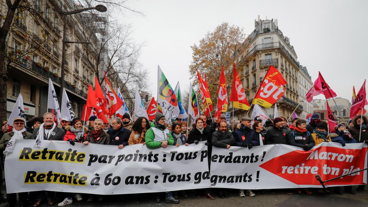 """People hold a banner reading """"Pension by points: we all lose. Retirement at 60: we all win"""" during a demonstration against a plan to overhaul national pensions in Paris."""