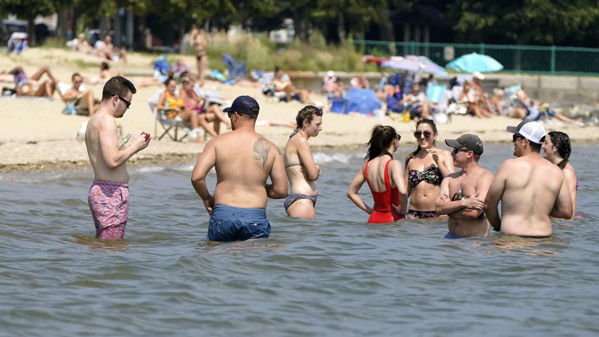 Beachgoers try to cool off Wednesday in the waters of Dorchester Bay in Boston.