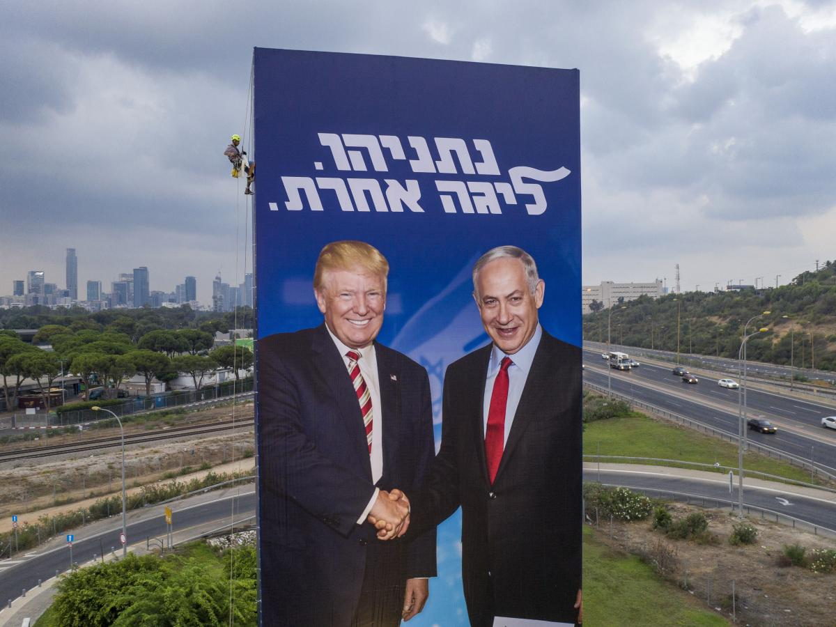 "A worker hangs a Likud party campaign billboard of Netanyahu and President Trump in Tel Aviv, Israel, on Sept. 8. The Hebrew message on the billboard reads ""Netanyahu, in another league."""