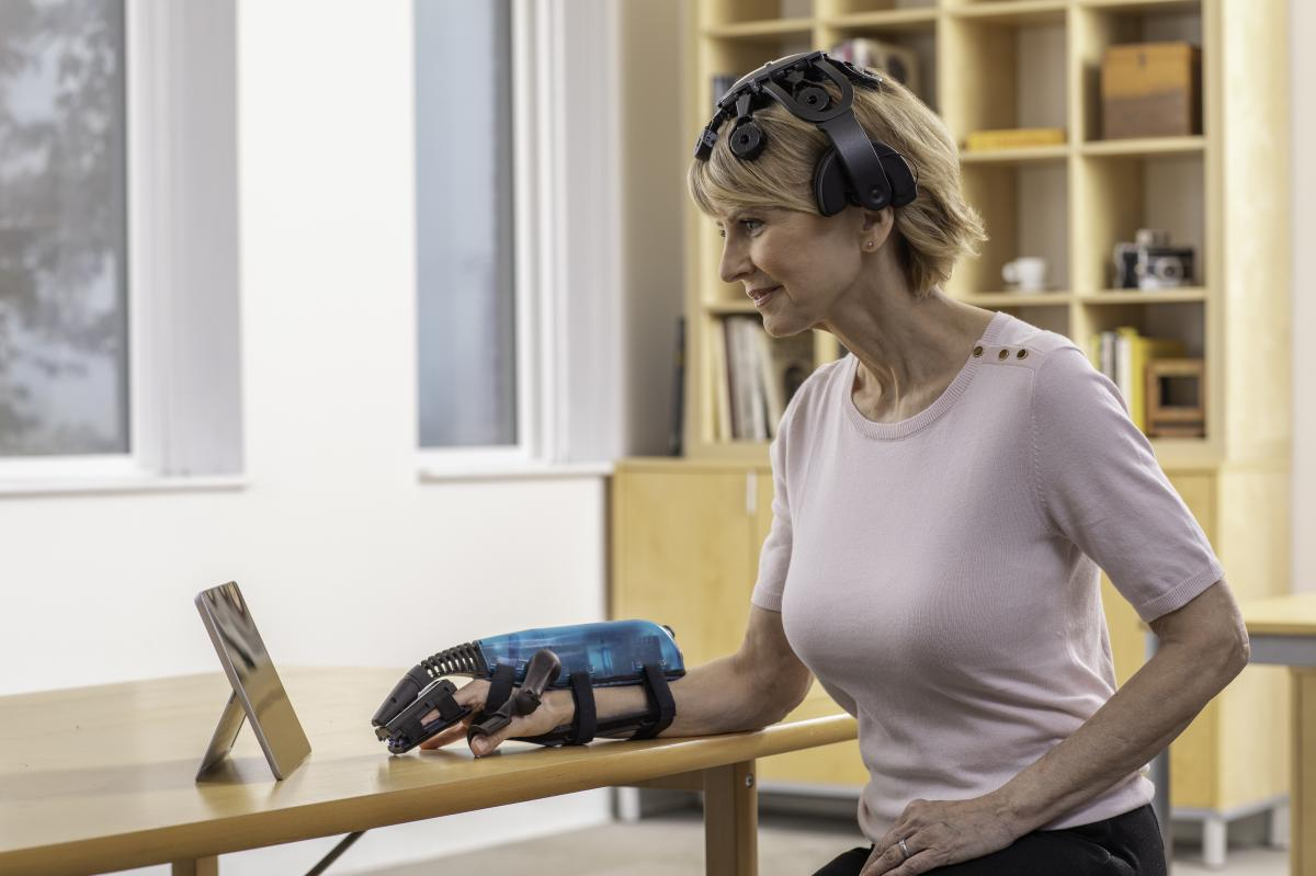 A woman demonstrates the IpsiHand rehabilitation device for stroke patients.