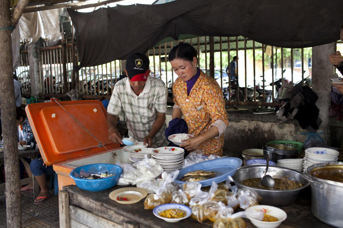Sriv Keng (right) and her husband, Vet Vong, dish up bowls of rice for customers at her roadside food stall, which is situated in a garment manufacturing district.