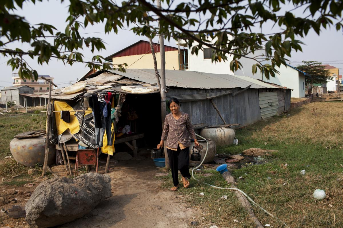 Eng Sreng, 63, the mother of Sriv Keng, carries teapots in front of the family's former home made of corrugated tin on the outskirts of Phnom Penh.