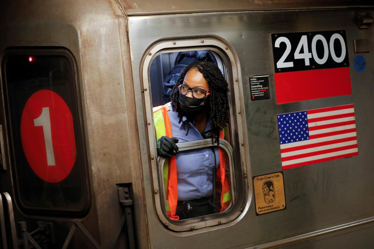 An MTA worker wears a protective mask while working on a subway train in New York City on Monday as coronavirus cases continue to rise, fueled by the virus's delta variant.