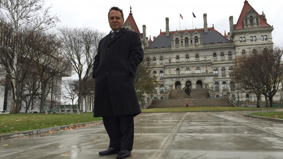 """Bruce Roter standing in front of the New York State Capitol, a place he says some would claim is """"the epicenter of all that's wrong with New York state government."""""""