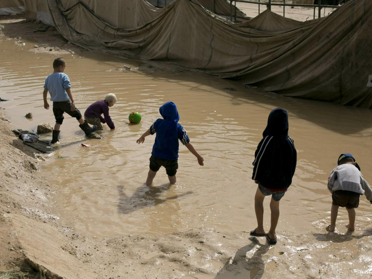 In this March 31, 2019 file photo, children play in a mud puddle in the section for foreign families at al-Hol camp in Hasakeh province, Syria.
