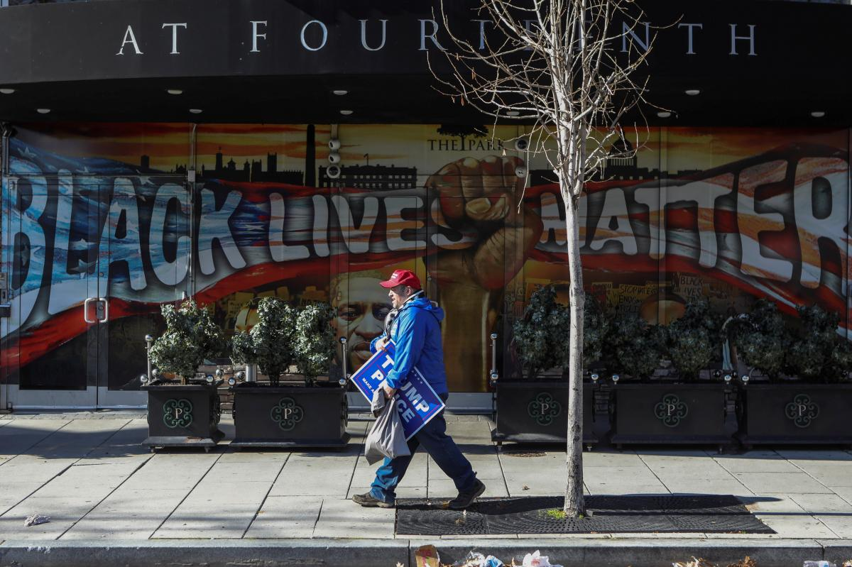 Joe Brunner, a supporter of former President Donald Trump, walks by a Black Lives Matter and George Floyd mural in Washington, D.C., on Wednesday.