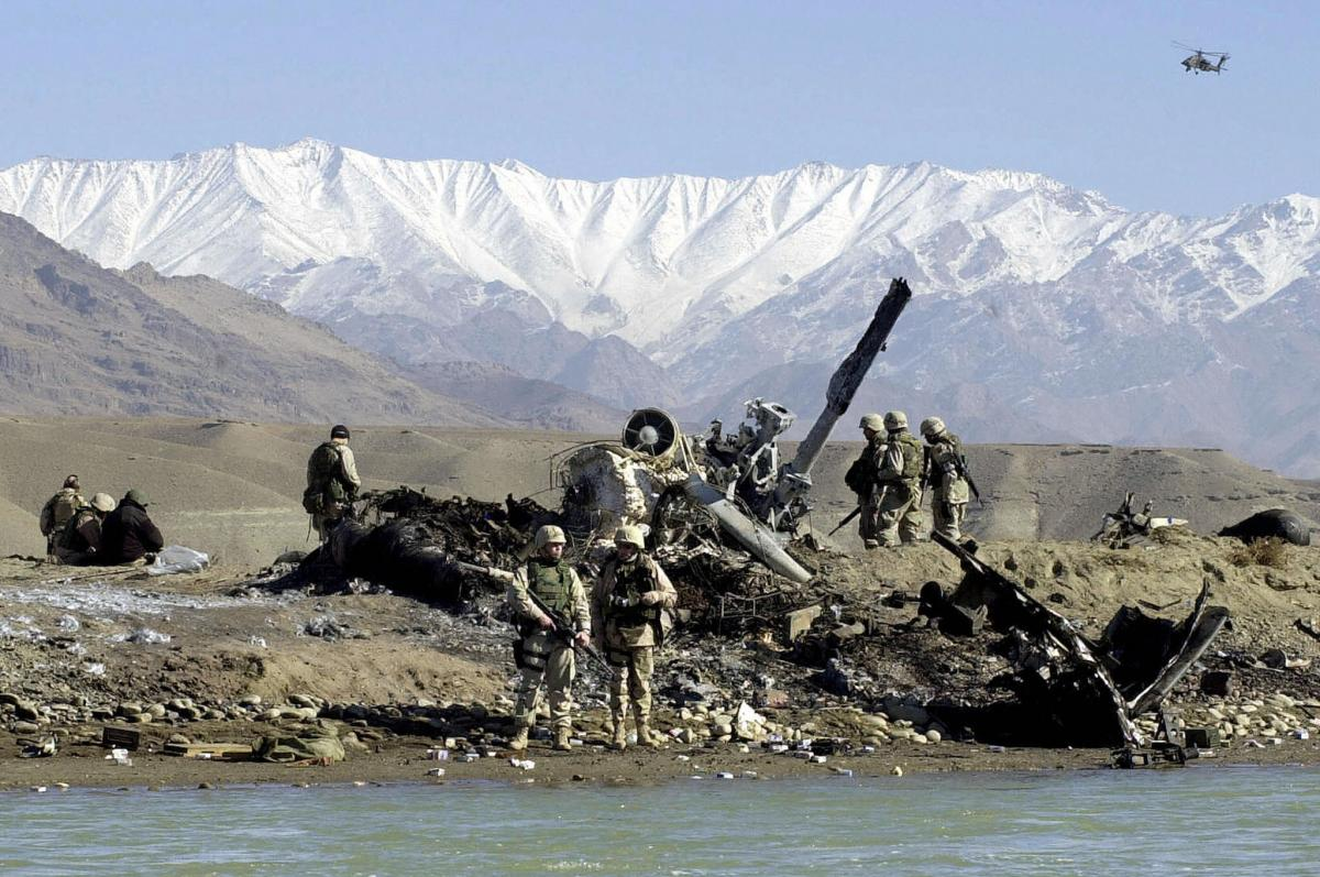 U.S. Army soldiers inspect the wreckage of a U.S. MH-53 Pave Low helicopter near Bagram Airfield on Nov. 24, 2003. Five soldiers were killed and seven others injured when the transport helicopter crashed while taking part in Operation Mountain Resolve, an