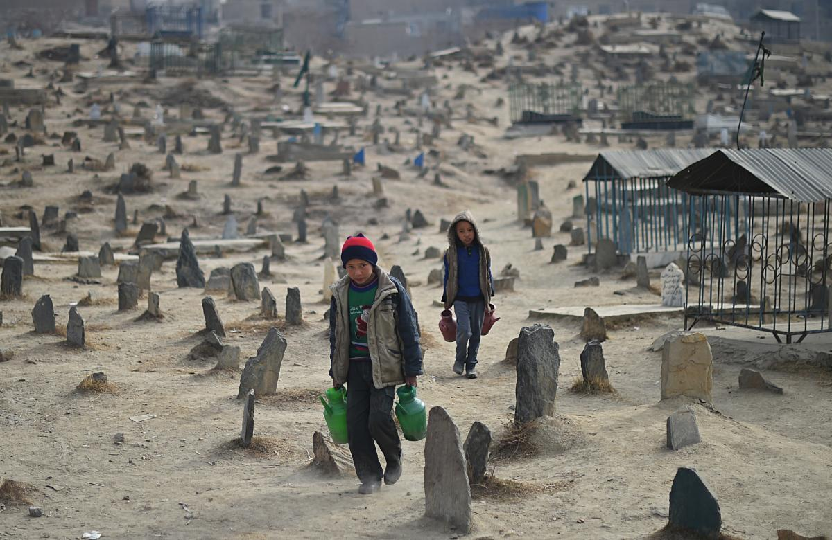 Afghan children who work as water vendors search for customers at the Kart-e-Sakhi cemetery in Kabul on Jan. 12, 2015. Thousands of victims of the country's civil war of the 1990s are buried in cemeteries across the Afghan capital.