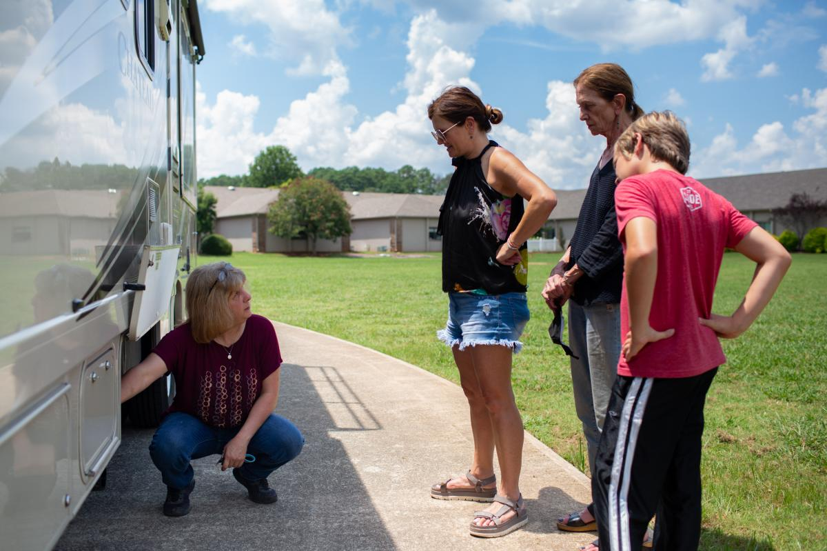 RV owner Cheryl Huettel shows the Holditch family the power and water hookups they will use in campgrounds along their way to Cape Cod. From left: Huettel, Amy Holditch, Sandra Gillis, and Duncan Holditch.