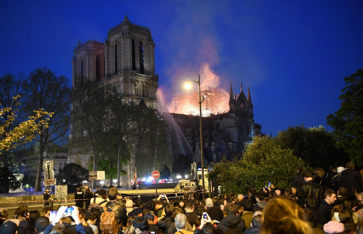 Crowds watch as flames and smoke billow from the cathedral's roof.
