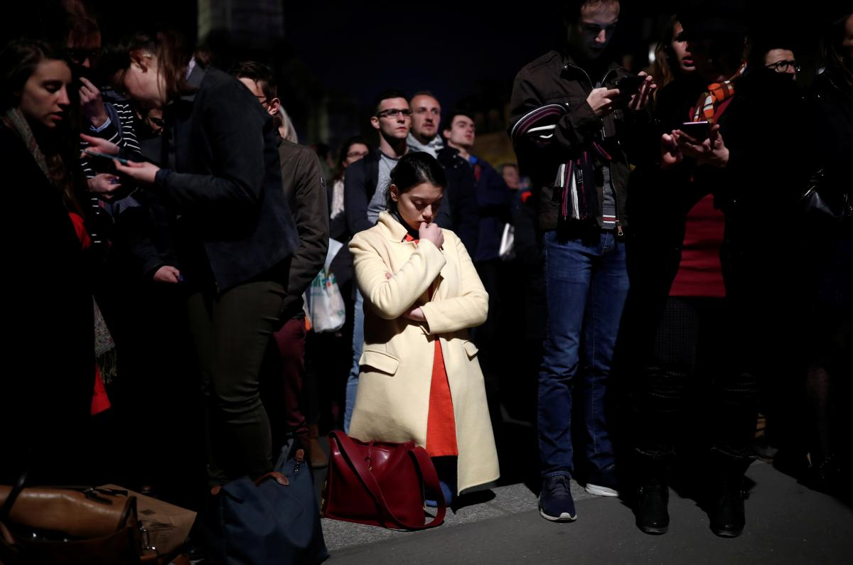 A woman prays next to Notre Dame after it sustained heavy damage from Monday's fire in Paris.