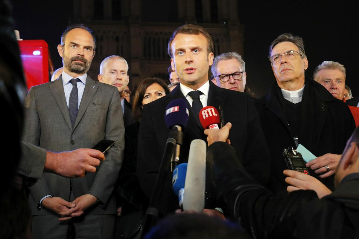 French President Emmanuel Macron speaks as Prime Minister Edouard Philippe and Archbishop of Paris Michel Aupetit stand near the cathedral.