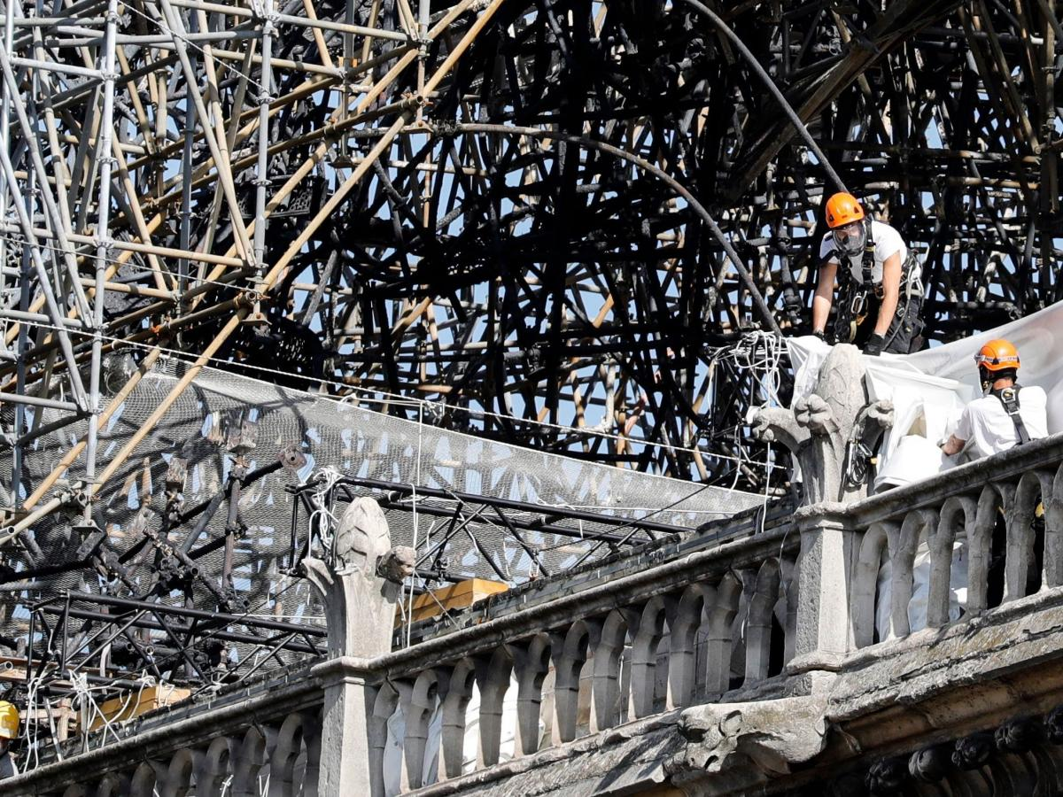 Workers wear masks as they survey the damaged area cathedral on Monday.