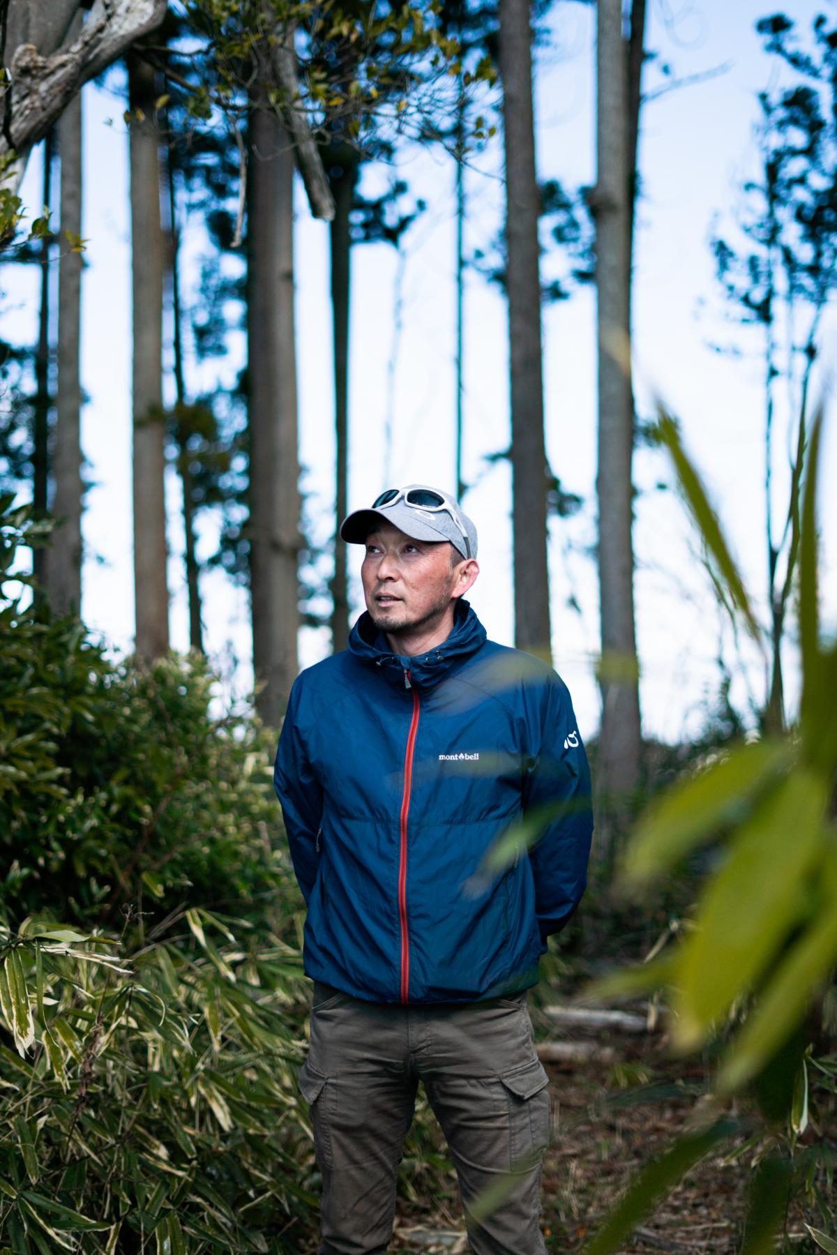 Takayuki Ueno stands in the trees behind his home where he discovered bodies of his mother and daughter after the tsunami in 2011.