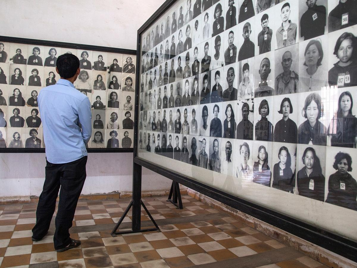 A Cambodian man stands by a wall of photographs of detainees of the Khmer Rouge regime in one of the rooms of Tuol Sleng prison, also known as S-21. Most of them were executed or died of overwork.
