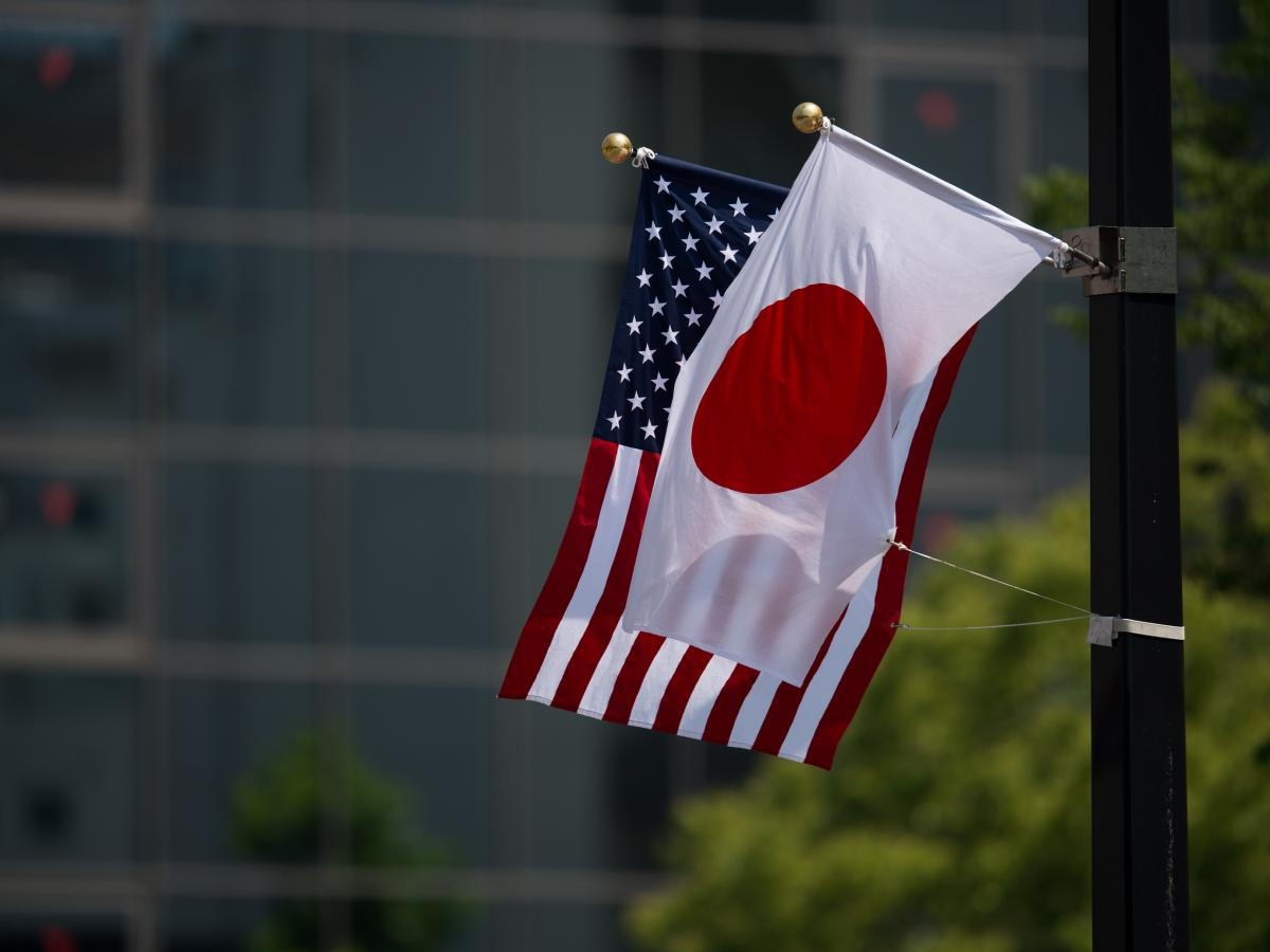 A Japanese and a U.S. flag are seen next to the Hiroshima Peace Memorial in Hiroshima on Friday.