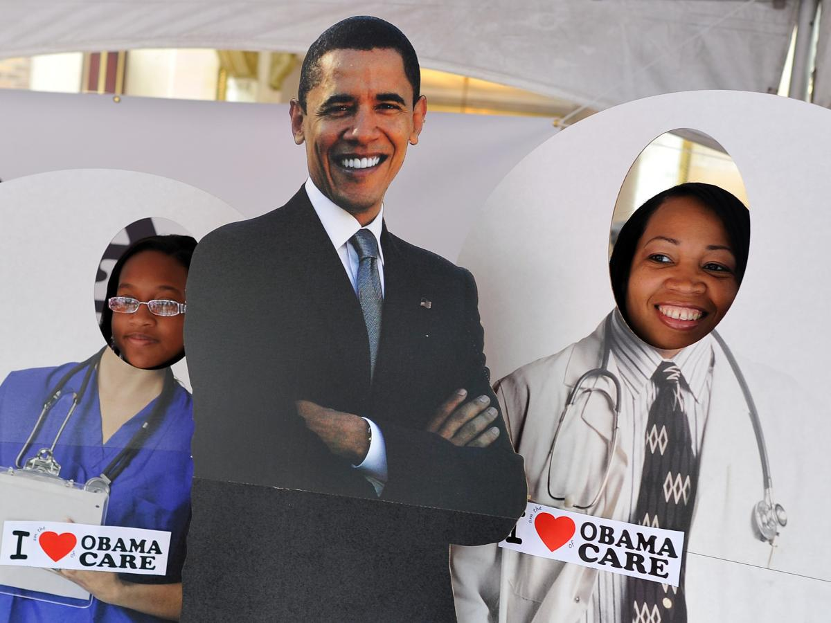 """Two girls pose for a picture with a cardboard cut-out of President Obama in a tent defending """"Obamacare"""" in Charlotte, N.C., on Sept. 3, 2012."""