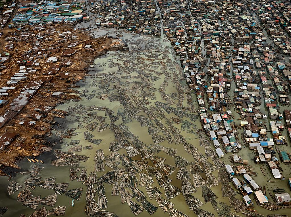 This aerial photo depicts the sawmills of Lagos, Nigeria. The timber from the country's rainforests, some of the most heavily deforested in the world, are processed in this coastal city, polluting the lagoons.