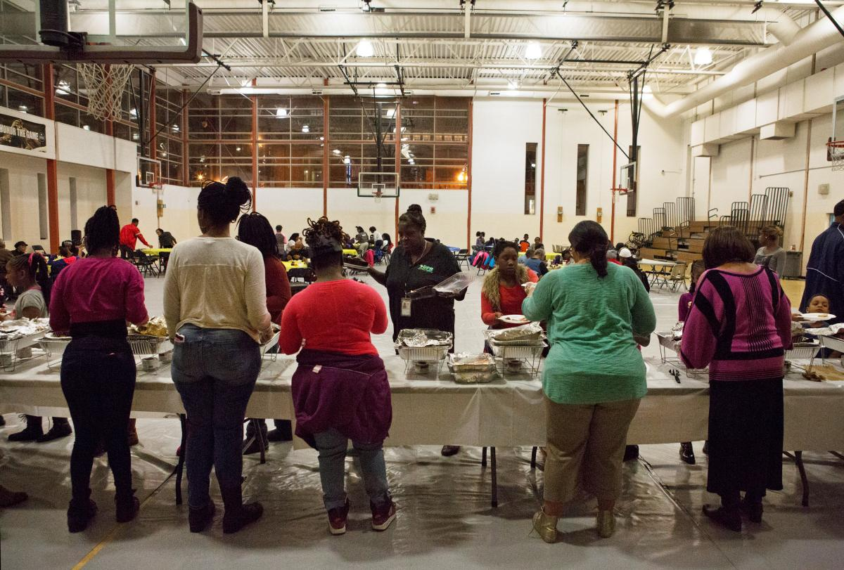 Residents line up for a Thanksgiving meal in a community gathering at Kennedy Recreation Center in Shaw.